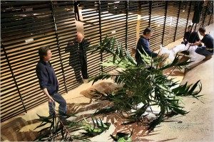Palm leaves being attached to the slats.